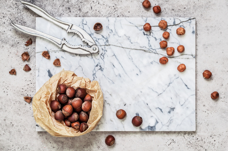 Selled and Unshelled Hazelnuts with Nutcrackers on a Marble Board, copy space for your text