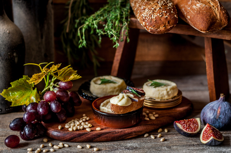 Soft Spreadable French Stinky Cheese on a Slice of Bread with Fruit and Pine Nuts Archivio Fotografico - 117961367