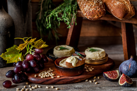 Soft Spreadable French Stinky Cheese on a Slice of Bread with Fruit and Pine Nuts Archivio Fotografico - 120212761