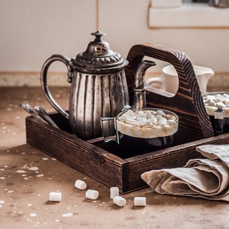 Kaffee mit Marshmallows auf einem Küchentisch in einem Holztablett Standard-Bild