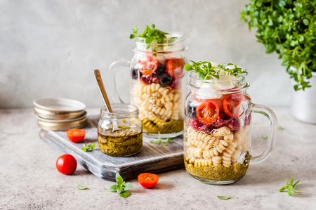 Italian Pasta Salad in a Jar with Salami, Cherry Tomatoes and Mini Mozzarella, copy space for text