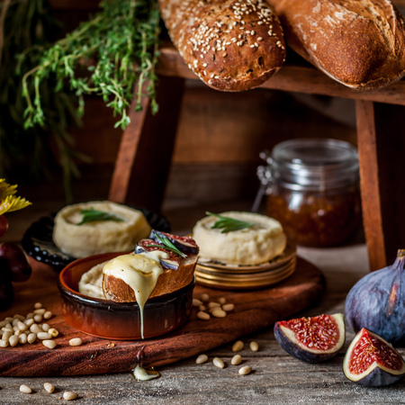 Soft Spreadable French Stinky Cheese on a Slice of Bread with Fruit and Pine Nuts Archivio Fotografico - 122005622