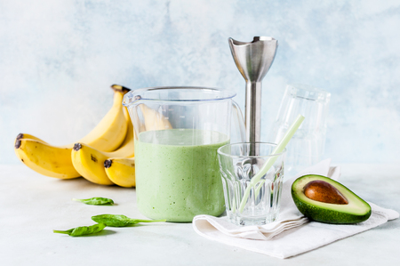 Healthy Green Smoothie Blended with a Hand Blender in a Measuring Cup from Avocado, Banana and Spinach