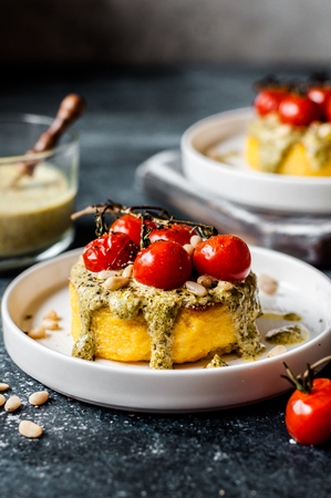 Fried Polenta Discs with Creamy Pesto Sauce and Roasted Cherry Tomatoes, copy space for your text