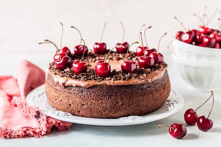 Pastel de chocolate decorado con virutas de chocolate y cerezas dulces