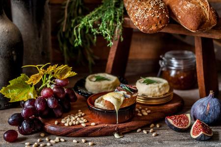 Soft Spreadable French Stinky Cheese on a Slice of Bread with Fruit and Pine Nuts Archivio Fotografico - 124305038