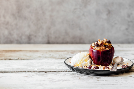 Baked Apple Stuffed with Walnuts and Sultanas Served with a Scoop of Ice Cream, copy space for your text