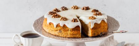 Sliced Pumpkin Cake with Walnuts and Cream Cheese Frosting, banner Stock Photo