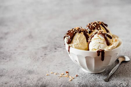 Vanilla Ice Cream Scoops with Chocolate Ganache and Chopped Nut Topping, copy space for your text Archivio Fotografico
