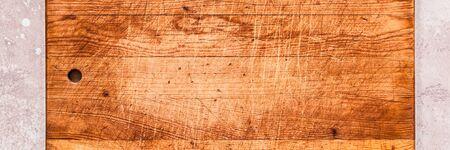 Tabla de cortar antigua sobre fondo de hormigón rosa, banner, espacio para copiar el texto