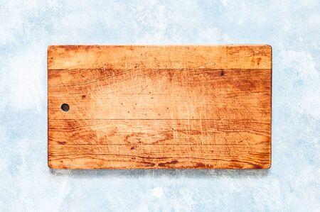 Vieille planche à découper sur fond de béton bleu, copiez l'espace pour votre texte