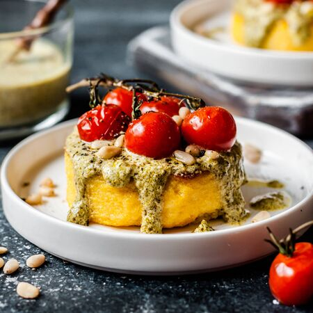Fried Polenta Discs with Creamy Pesto Sauce and Roasted Cherry Tomatoes, square Stock fotó