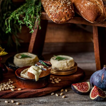 Soft Spreadable French Stinky Cheese on a Slice of Bread with Fruit and Pine Nuts, square Archivio Fotografico - 127988452