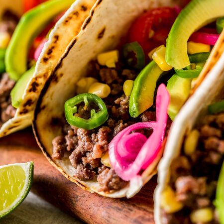 Mexican Minced Beef Tacos with Vegetables and Corn Salsa, close up, square