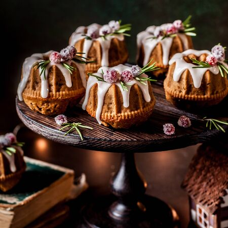 Mini Christmas Bundt Cakes Decorated with Sugared Cranberries and Rosemary, copy space for your text