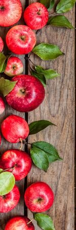 Ripe Red Apples with Leaves, Old Wood Background