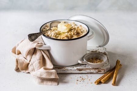 Cinnamon Old Fashioned Rolled Oat Porridge with Melting Butter in a Sauce Pan Topped with Chopped Almond Nuts