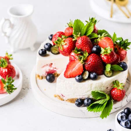 Sliced No Bake Berry Cheesecake Decorated with Fresh Strawberries and Blueberries, square