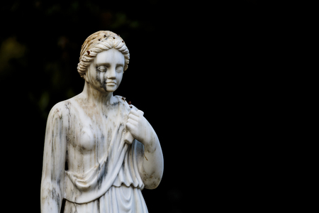 downcast: Historical statue of a young woman in Maria Luisa Park in Seville, Spain With downcast eyes Against a dark background with copyspace