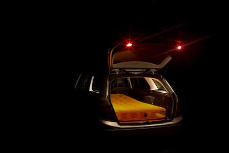 station wagon: Night view of an illuminated open car boot on an estate car or station wagon with a mattress inside