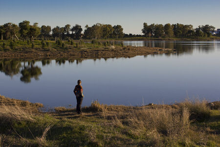facing away: Lone person standing facing away from the camera looking out over a tranquil lake with reflections in early morning light Stock Photo