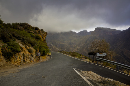 diverging: Atmospheric landscape of converging tarred mountain roads in mist under a heavy threatening grey sky Stock Photo