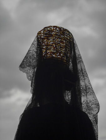 Woman wearing a headdress of black Spanish lace lifted high on a traditional comb standing with her back to the camera agaisnt a cloudy grey sky during a Holy Week in Andalucia, Spain Stock Photo