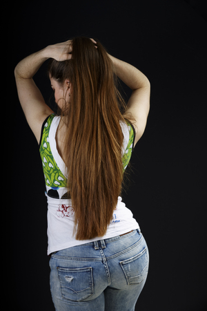 Sexy curvaceous young woman with long straight brunette hair viewed from behind showing off her curvy bottom in denim jeans against a dark background
