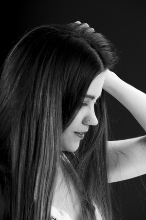 introspective: Close up Long Hair Pretty Young Woman in Side View with One Hand Touching her Hair. Captured in Monochrome Style.