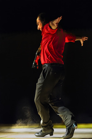 concentrates: Energetic man in a colourful red shirt dancing flamenco outdoors at night with his outspread arms flung backwards as he concentrates on his steps in the darkness Stock Photo
