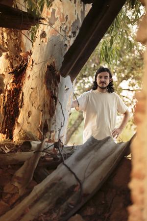 nonchalant: Long Hair Man iLong Hair Young Man in Casual White Shirt Behind Big Tree, Looking at the Camera.n White Behind the Tree Stock Photo