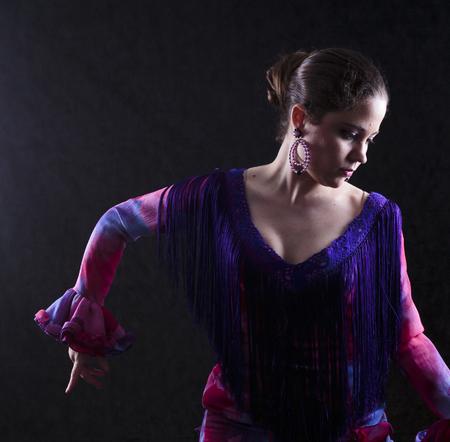 bailando flamenco: Close up Gorgeous Mujer joven que presenta en rojo elegante violeta Vestimenta Mientras que el baile flamenco, Orientaci�n de la Cara. Capturado en estudio en fondo gris abstracto.