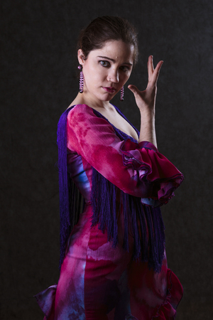 Graceful sensual woman in an elegant magenta evening dress standing sideways raising her hand in the air and looking enticingly at the camera in a dark evocative portrait photo