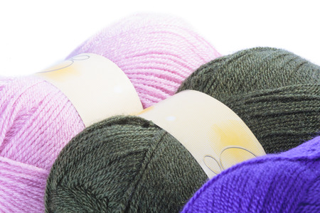Three balls of coloured wool in pink, charcoal and purple for knitting a garment, close up view over white photo