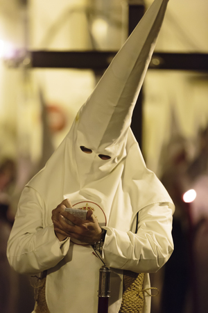 holy week in seville: Religious Catholic penitent dressed in a conical hat and robes standing writing notes during the Holy Week procession in Seville, Spain Editorial