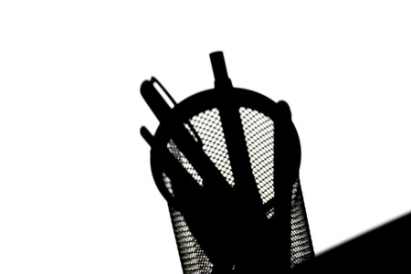 desk tidy: Low angle view of the silhouette of a cylindrical wire mesh desk tidy with ballpoint pens on the edge of a table on white