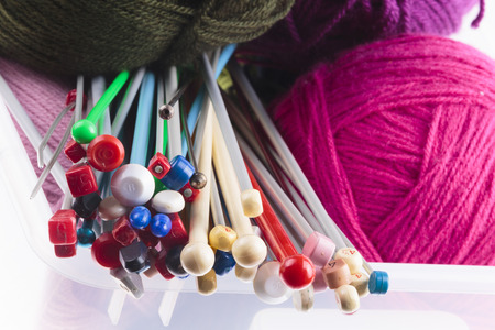 knitting needles: Collection of assorted sizes of modern plastic knitting needles with colorful balls of magenta, purple and charcoal grey wool viewed from the tops Stock Photo