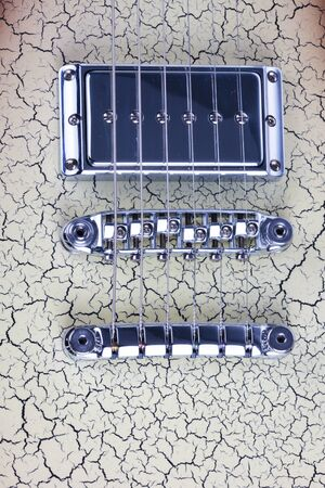 intonation: Close up overhead view of the silver metal bridge on an electric guitar showing detail of the six strings and saddle for adjusting intonation on the patterned body of the musical instrument