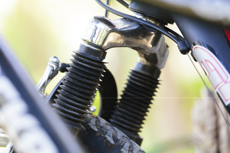 Close up on suspension fork element with brake and gear shifting cables for bicycle