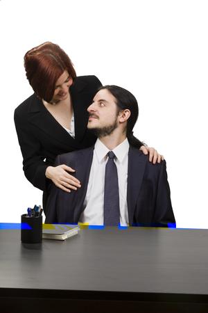 seated man: Pares del asunto - Mujer Feliz Detrás de hombre sentado a su mesa de trabajo mientras que mira uno al otro. Aislado en el fondo blanco. Foto de archivo