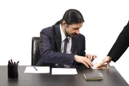 Businessman accepting a bribe in payoff for his corrupt services as a woman places cash on his desk which he eagerly accepts Stock Photo
