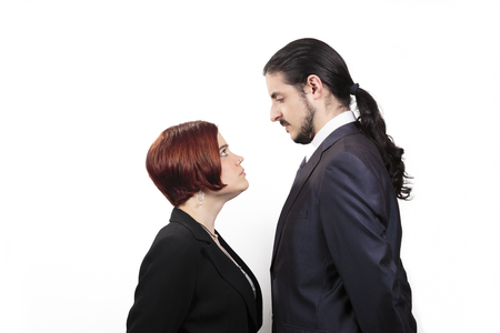 Stand off between a male and female partner with the shorter woman staring up belligerently into the face of the man in a suit with a ponytail, profile view on white