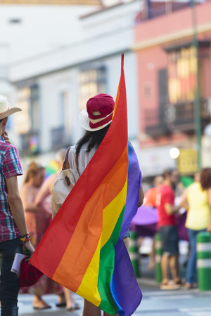 Rear view of unidentifiable person in hat holding gay pride flag in street during a meeting or parade Stock Photo