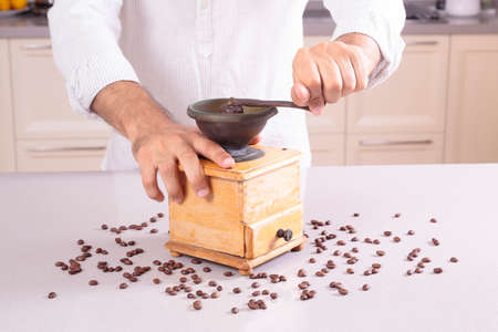 Caucasian man in white clothes grinding coffee Imagens