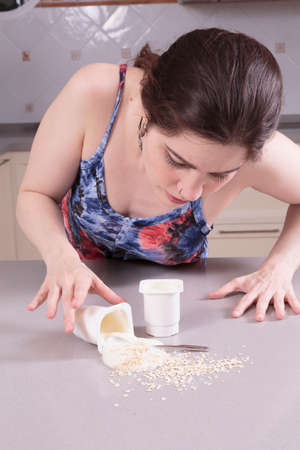 Young woman cleaning yoghurt and cereals spilt left by somebody else