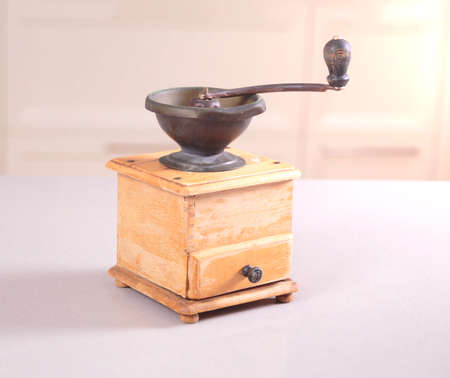 Old obsolete manual coffee grinder made of wood and iron