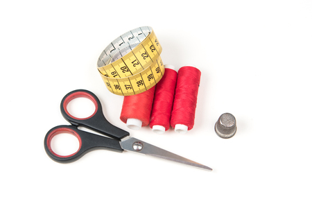 Red sewing threads, small closed black scissors, yellow measuring tape and metal thimble on white background
