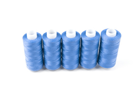 Five light blue sewing threads on white background, surface Stock Photo