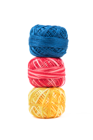 Three colored sewing threads in a row on a white background. Blue, red and yellow threads