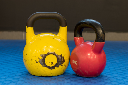 Red and yellow used and old kettlebells on a blue background. Workout equipment